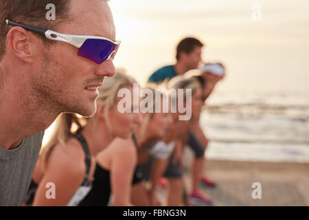 Closeup shot of focused and determined young man standing at starting line with competitors in background. Runners - Stock Photo