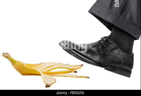 male foot in the left black shoe slips on a banana peel isolated on white background - Stock Photo
