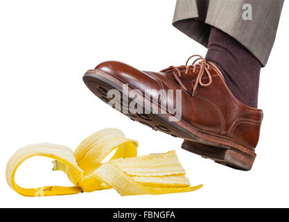 male foot in the left brown shoe slips on a banana peel isolated on white background - Stock Photo