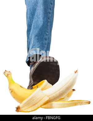 male left leg in jeans and brown shoe stepping on banana isolated on white background - Stock Photo