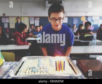 Birthday Boy Standing In Front Of Lit Cake In Classroom - Stock Photo