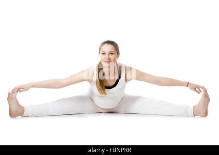 Full length portrait of smiling young pregnant fitness model in sportswear, doing yoga, pilates training, Wide-Angle - Stock Photo