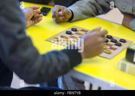 Two unidentifiable men play a game of draughts (US - checkers) at a community centre  Photo credit : Chris Bull - Stock Photo