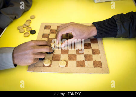 Two unidentifiable men play a game of draughts (US - checkers) at a community centre - Stock Photo