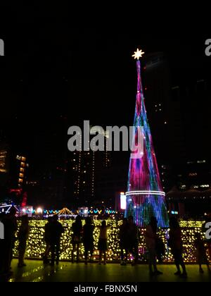 Group Of People In Front Of Illuminated Buildings At Night - Stock Photo