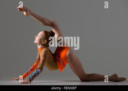Attractive gymnast athlete teenage girl wearing dancer colorful leotard working out, dancing, posing, doing backbend, - Stock Photo