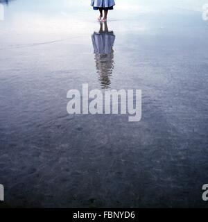 Low Section Of Woman Walking On Water With Reflection - Stock Photo