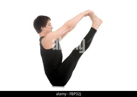 Sporty young man doing yoga or pilates exercises, sitting in Ubhaya Padangusthasana, Both Feet Big Toe, Double toe - Stock Photo