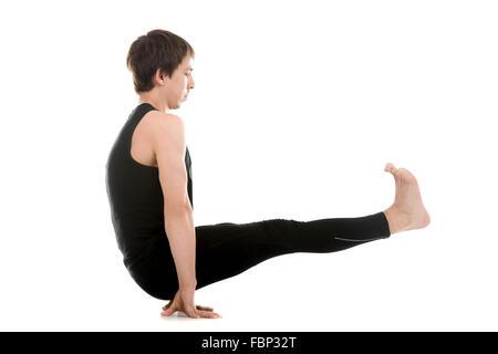 Sporty young man doing yoga or pilates arm balancing exercises, Utpluti Dandasana (Floating Stick asana), Celibates - Stock Photo