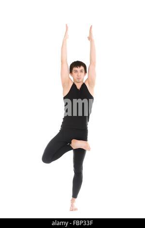 Sporty young man doing yoga, pilates, fitness training, exercise for spine, standing in Tree Pose, asana vrikshasana, - Stock Photo