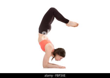Profile of sporty yogi girl doing fitness exercises, yoga asana Scorpion Pose Vrischikasana 1 posture, forearm stand, - Stock Photo