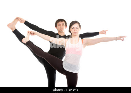 Two sporty people practice yoga with partner, couple doing stretching exercise, Extended Hand to Big Toe yoga pose, - Stock Photo