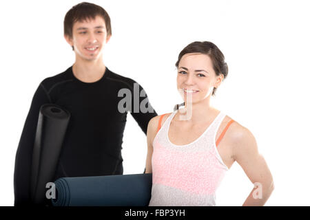 Portrait of happy smiling young man and woman holding folded yoga, pilates mats, sporty couple before exercising - Stock Photo