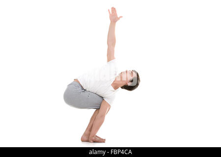 Sporty young man working out, standing in variation of Revolved Chair twist Pose, Parivrtta utkatasana with extended - Stock Photo