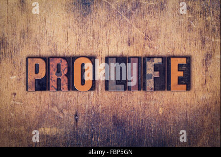The word 'Pro Life' written in dirty vintage letterpress type on a aged wooden background. - Stock Photo