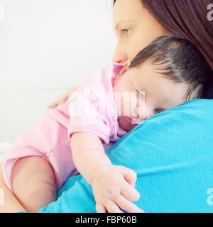 Side View Of Mother Holding Cute Baby Against White Background - Stock Photo