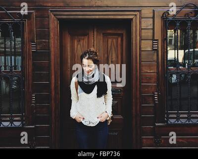 Portrait Of Young Woman In Front Of Wooden Building - Stock Photo