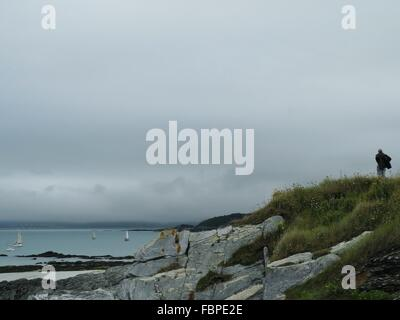 Man Standing On Rock Overlooking Sea - Stock Photo