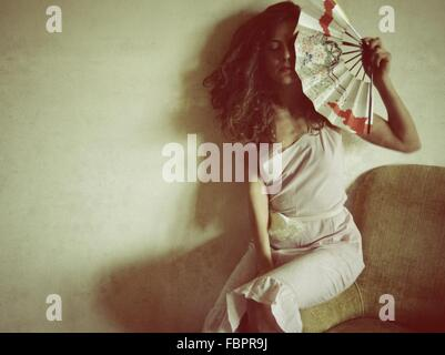 Young Woman Holding Hand Fan While Sitting On Sofa Against Wall - Stock Photo