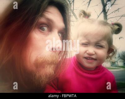 Close-Up Portrait Of A Man And Baby Girl Making Faces - Stock Photo