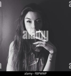 Portrait Of Young Woman Smoking Against Plain Background - Stock Photo