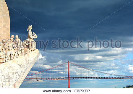 Detail of the Monument to Discoveries located along the Tagus River in Belém with iconic Lisbon bridge in the background - Stock Photo