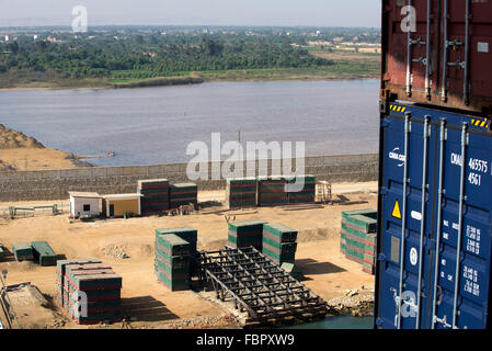 View from container ship of building materials on construction site stacked alongside the waterway of the Suez Canal - Stock Photo