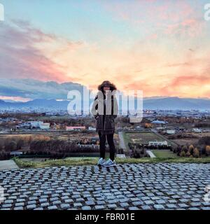 Full Length Of Woman In Hooded Jacket Standing Against Cityscape During Sunset - Stock Photo