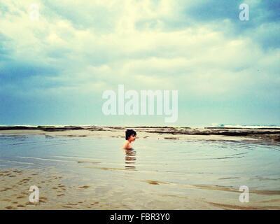 Shirtless Boy Swimming In Sea - Stock Photo