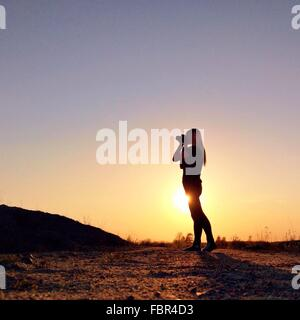 Silhouette Woman Photographing Landscape At Sunset - Stock Photo