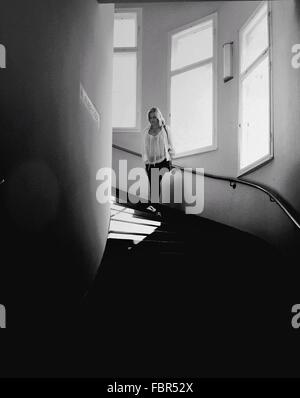 Full Length Of Young Woman Walking Down Stairs - Stock Photo