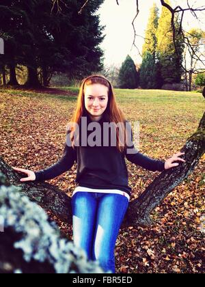 Portrait Of Happy Young Woman Sitting On Branch In Park