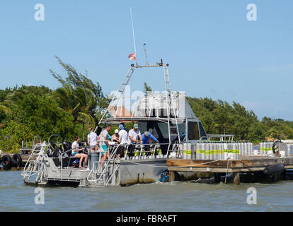 Dive boat with divers preparing to depart the dock and air tanks lined up on dock, Ocean frontiers, East End, Grand - Stock Photo