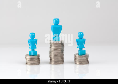 One male and two female figurines standing on piles of coins. Income inequality concept. - Stock Photo