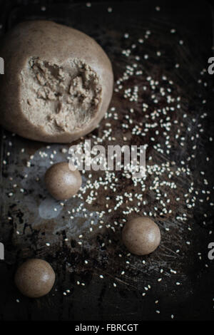 Work in progress for tahini cookies: making small balls with dought - Stock Photo