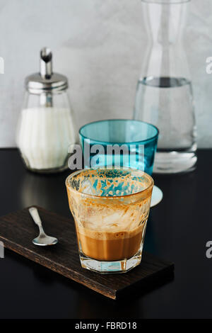 Coffee and a glass of water on a restaurant table - Stock Photo