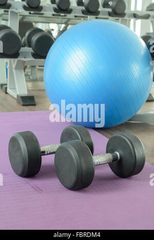There are equipment for excercise in gym. (e.g. Rubber dumbbells, yoga ball, and yoga mat) - Stock Photo