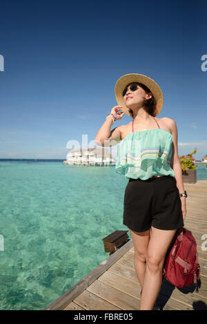slim woman wearing hat and sunglasses posting on wooden bridge over the clear sea water at Maldives on a sunny day - Stock Photo