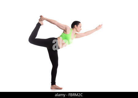Beautiful sporty girl practices yoga, performing Natarajasana, Lord of the Dance pose, balance workout, full body - Stock Photo