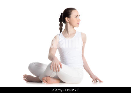 Sporty beautiful young woman in white sportswear practicing yoga, sitting cross legged in Revolved easy pose, spinal - Stock Photo