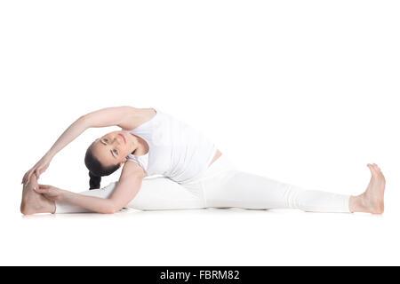 Sporty smiling beautiful young woman in white sportswear sitting in advanced variation of Parivrtta Upavistha Konasana, - Stock Photo
