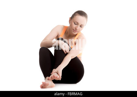 Young athlete girl in sportswear rubbing her foot, injured after sport exercises, feeling pain in ligament, sprained - Stock Photo