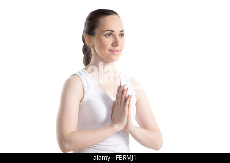 Portrait of smiling beautiful sporty young woman in white sportswear holding palms in Namaste gesture, studio full - Stock Photo
