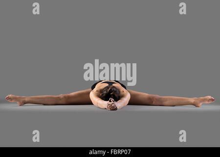 Beautiful young fit woman in sportswear doing sport exercise, Upavishtha Konasana, Wide-Angle Seated Forward Bend, - Stock Photo