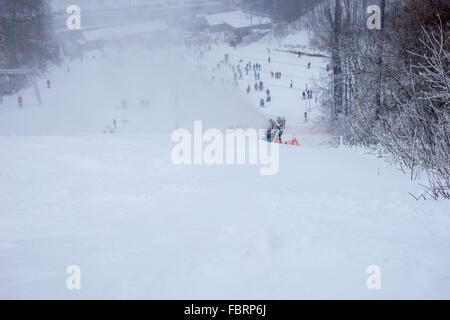 Plume of snow in mid air as skier goes downhill at winter ski resort during storm - Stock Photo