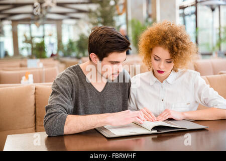 Portrait of a young couple reading menu in restaurant - Stock Photo