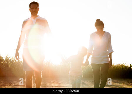Family with little boy walking together outdoors - Stock Photo