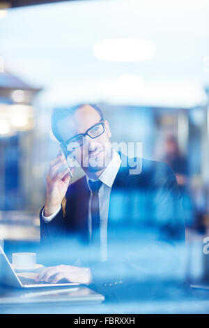 Confident businessman speaking on the phone and networking in cafe - Stock Photo