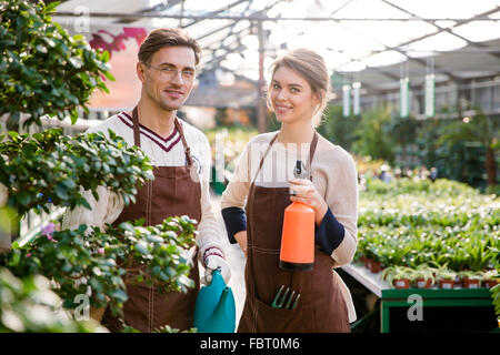 Happy man and woman gardeners holding watering can and pulveriser for spraying flowers and plants in greenhouse - Stock Photo