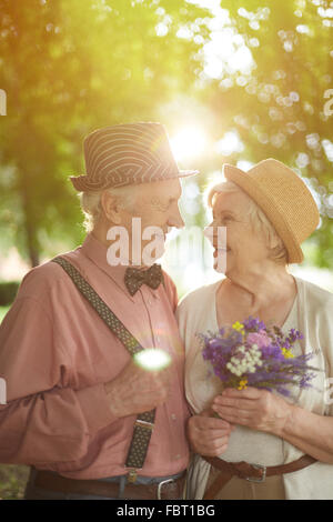 Amorous seniors looking at one another with smiles in natural environment - Stock Photo